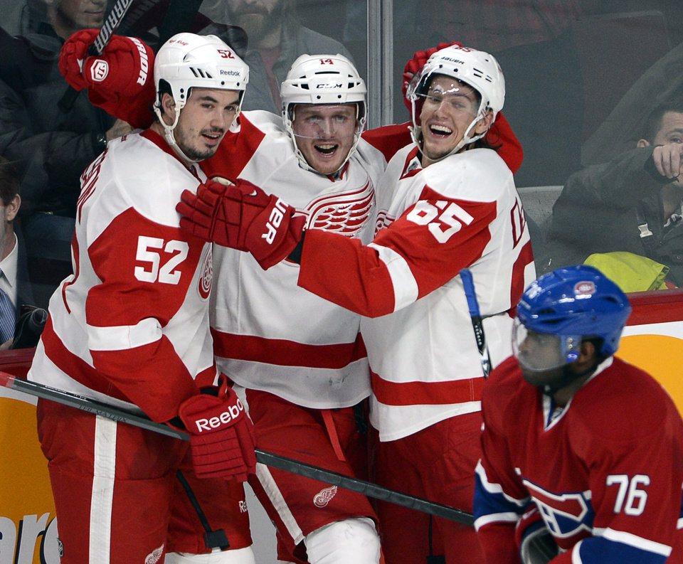 Photo - Detroit Red Wings center Gustav Nyquist (14) celebrates his winning goal with defensemen Jonathan Ericsson (52) and Danny DeKeyser (65) as Montreal Canadiens defenseman P.K. Subban (76) skates by during overtime in an NHL hockey game Wednesday, Feb. 26, 2014, in Montreal. Detroit won 2-1. (AP Photo/The Canadian Press, Ryan Remiorz)