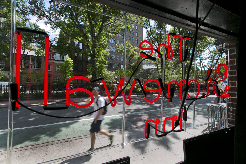 Photo - A neon sign fills the window of The Stonewall Inn, in New York's Greenwich Village, Thursday, May 29, 2014. The National Park Service is launching an initiative to make places and people of significance to the history of lesbian, gay, transgender and bisexual Americans part of the national narrative. Interior Secretary Sally Jewell plans to announce the initiative on Friday at New York's Stonewall Inn, which was made a national historic landmark in 2000.(AP Photo/Richard Drew)