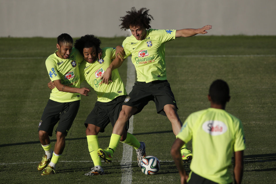 Photo - Brazil's Neymar, left, Marcelo, center, and David Luiz joke during a training session in Fortaleza, Brazil, Thursday, July 3, 2014. Brazil will face Colombia on Friday in a quarterfinal soccer match at the World Cup. (AP Photo/Felipe Dana)