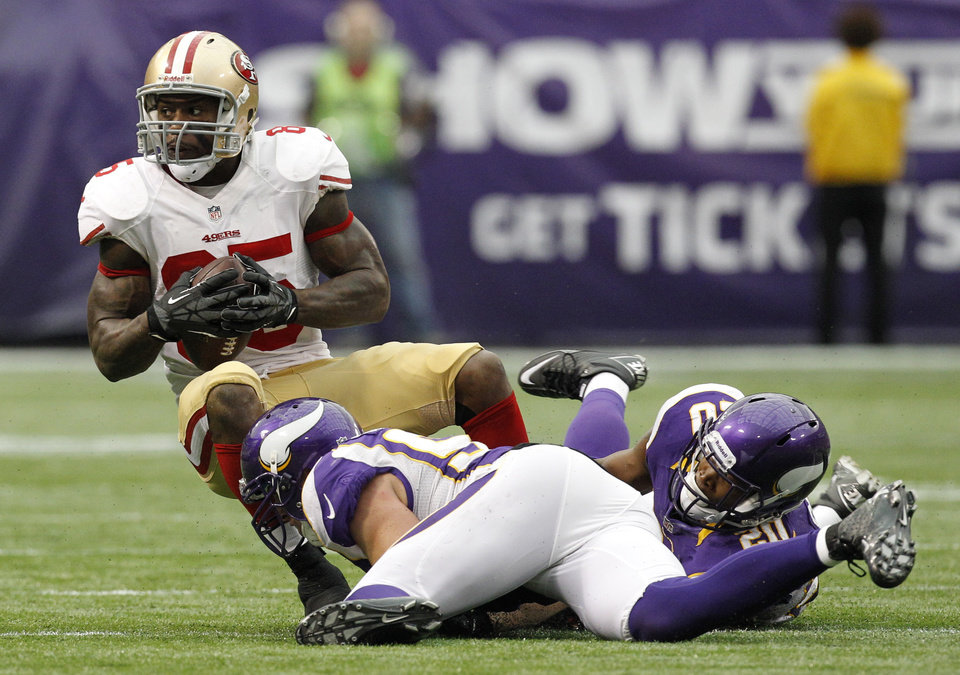 Photo -   San Francisco 49ers tight end Vernon Davis, top, is tackled by Minnesota Vikings outside linebacker Chad Greenway and cornerback Chris Cook, right, after making a reception during the second half of an NFL football game Sunday, Sept. 23, 2012, in Minneapolis. The Vikings won 24-13.(AP Photo/Genevieve Ross)