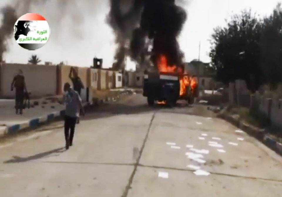 Photo - This image made from video posted by Iraqi0Revolution, a group supporting the al-Qaida breakaway Islamic State of Iraq and the Levant (ISIL) on Wednesday, June 11, 2014, which has been verified and is consistent with other AP reporting, shows militants on Al-Sharqat base north of Tikrit, Iraq. The al-Qaida-inspired group that led the charge in capturing two key Sunni-dominated cities in Iraq this week has vowed to march on to Baghdad, raising fears about the Shiite-led government's ability to slow the assault following lightening gains. Fighters from ISIL on Wednesday took Saddam Hussein's hometown of Tikrit, as soldiers and security forces abandoned their posts and yielded ground once controlled by U.S. forces. (AP Photo/Iraqi0Revolution via AP video)