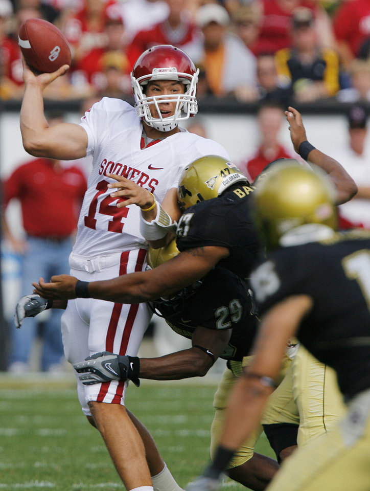 Photo - Oklahoma quarterback Sam Bradford (14) gets hit by the Colorado defense as he throws the ball during the first half of the college football game between the University of Oklahoma Sooners (OU) and the University of Colorado Buffaloes (CU) at Folsom Field on Saturday, Sept. 28, 2007, in Boulder, Co. 