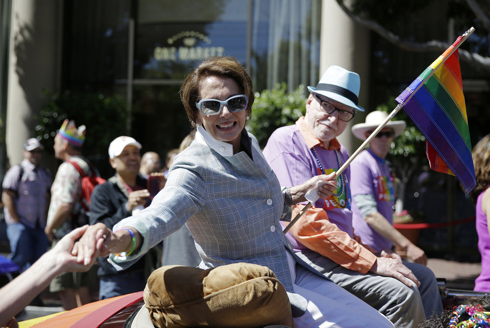 Photo - House Minority Leader Nancy Pelosi shakes hands while riding in the 44th annual San Francisco Gay Pride parade Sunday, June 29, 2014, in San Francisco. The lesbian, gay, bisexual, and transgender celebration and parade is one of the largest LGBT gatherings in the nation. (AP Photo/Eric Risberg)