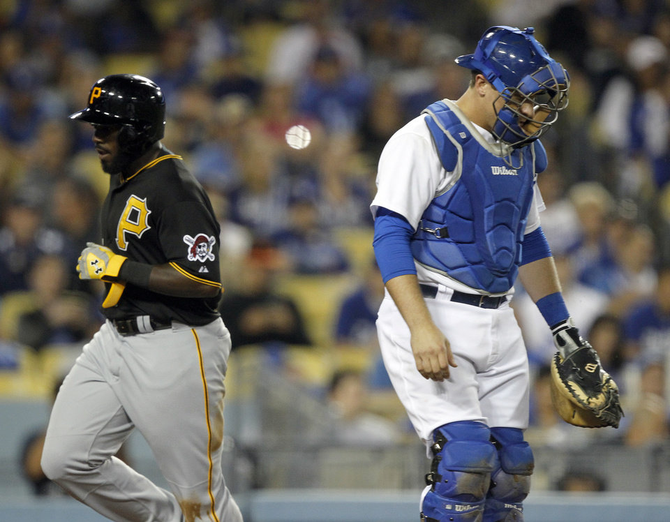 Pittsburgh Pirates' Josh Harrison, left, scores behind Los Angeles Dodgers catcher Tim Federowicz, right, on a single by Neil Walker in the seventh inning of a baseball game on Thursday, May 29, 2014 in Los Angeles. (AP Photo/Alex Gallardo)