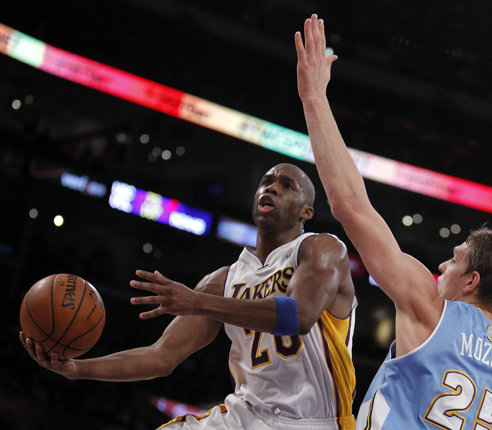 Photo - Los Angeles Lakers guard Jodie Meeks, left, lays up a shot against Denver Nuggets center Timofey Mozgov, right, of Russia during the first half of an NBA basketball game, Sunday, Jan. 5, 2014, in Los Angeles. (AP Photo/Alex Gallardo)