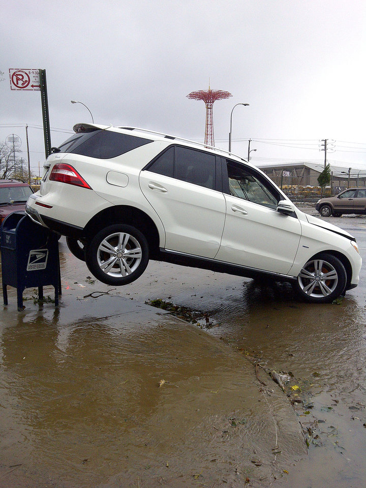 A car is upended on a mailbox on Surf Avenue in Coney Island, N.Y., in the aftermath of Sandy on Tuesday, Oct. 30, 2012. Sandy, the storm that made landfall Monday, caused multiple fatalities, halted mass transit and cut power to more than 6 million homes and businesses. (AP Photo/Ralph Russo) ORG XMIT: RPRR801