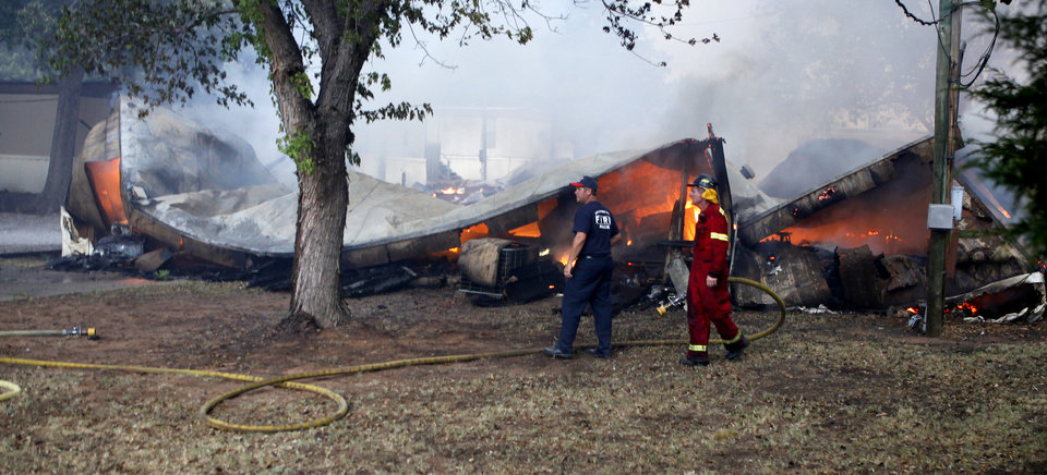 Photo - Firefighters walks past the burned remains of a mobile home Coffee Creek Mobile Home Park Edmond, Okla., Saturday, August 6, 2011. Photo by Bryan Terry, The Oklahoman