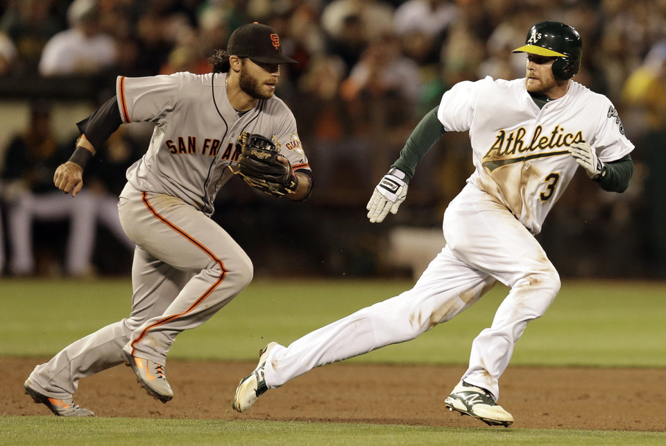 Photo - San Francisco Giants shortstop Brandon Crawford, left, chases Oakland Athletics' Craig Gentry in the fifth inning of a baseball game Tuesday, July 8, 2014, in Oakland, Calif. Crawford tagged out Gentry in the rundown between second and third base. (AP Photo/Ben Margot)