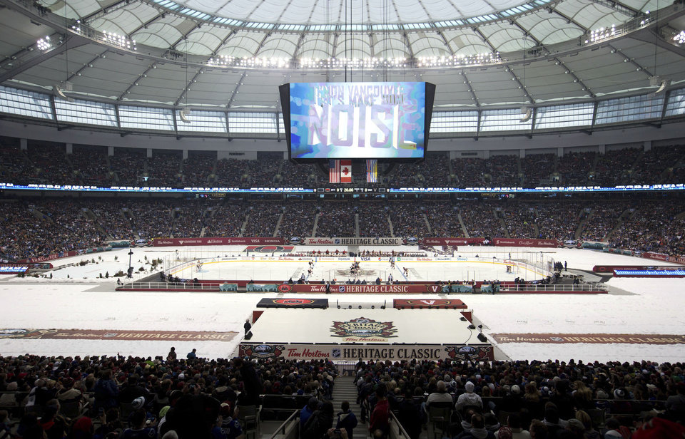 Photo - The Vancouver Canucks and Ottawa Senators take the opening face-off of an NHL Heritage Series hockey game in Vancouver, British Columbia, on Sunday, March 2, 2014. (AP Photo/The Canadian Press, Darryl Dyck)