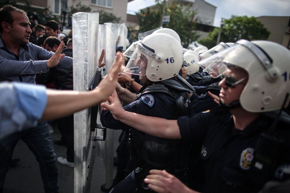 Photo - Riot police try to stop protesters who were attacking the offices of Prime Minister Recep Tayyip Erdogan's Justice and Development Party, in Soma, Turkey, during his visit to the coal mine in Soma Wednesday, May 14, 2014.  A violent protest erupted Wednesday in the Turkish city of Soma, where at least 238 coal miners have died after a mine explosion as many in the crowd expressed anger at Prime Minister Recep Tayyip Erdogan's government, rocks were thrown and some people were shouting that Erdogan was a