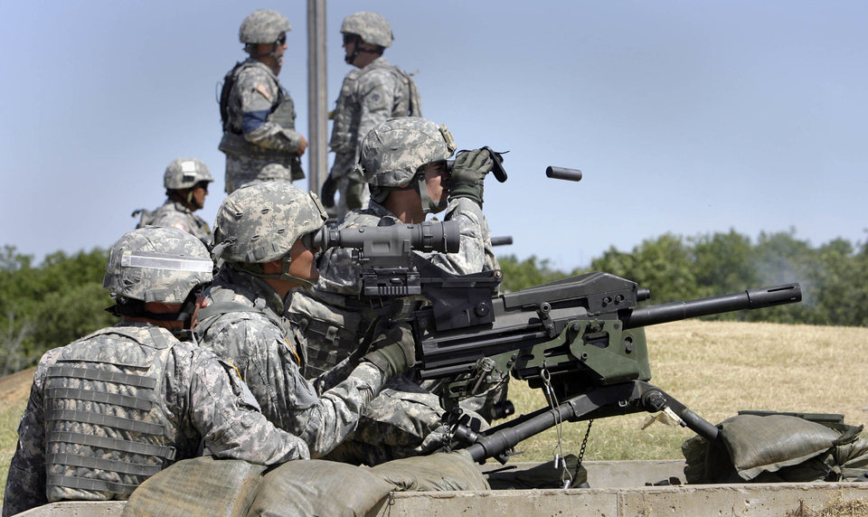 Photo - 1st Sgt. Johnny Paxon of Tecumseh, OK, a range NCO in-charge, looks on as Spc. George Alvarado of Woodward, OK, aims using an IR nigh scope while Pfc. Brian Bell of Okmulgee, OK, spots targets as they qualify on the Mk 19 automatic 40mm grenade launcher during training at Camp Gruber near Braggs, OK, June 12, 2012. Alvarado and Bell are deploying later this summer with nearly 200 other soldiers as Task Force Outlaw, with the Oklahoma Army National Guard, 120th Engineer Battalion to southern Afghanistan. MICHAEL WYKE/Tulsa World ORG XMIT: DTI1206121523034655