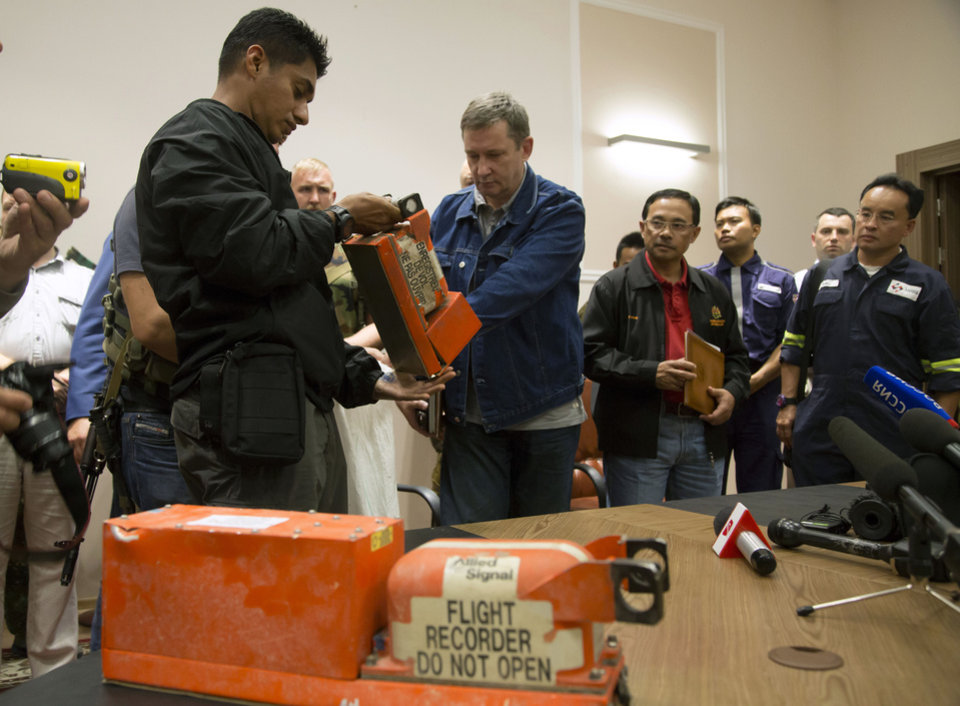 Photo - A Malaysian investigator, left, takes a black box from Malaysia Airlines Flight 17 as it is handed over by a Donetsk People's Republic official in the city of Donetsk, eastern Ukraine Tuesday, July 22, 2014. Bowing to international pressure Monday, pro-Moscow separatists released a train packed with bodies and handed over the black boxes from the downed Malaysia Airlines plane, four days after it plunged into rebel-held eastern Ukraine. (AP Photo/Dmitry Lovetsky)
