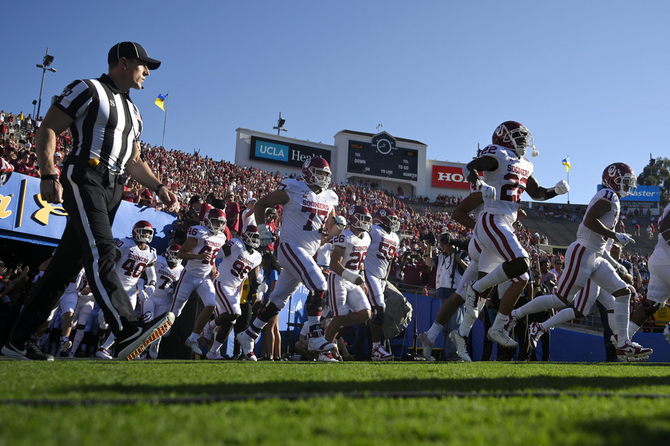 Photo - Oklahoma team members run onto the field for the team's NCAA college football game against UCLA on Saturday, Sept. 14, 2019, in Pasadena, Calif. (AP Photo/Mark J. Terrill)
