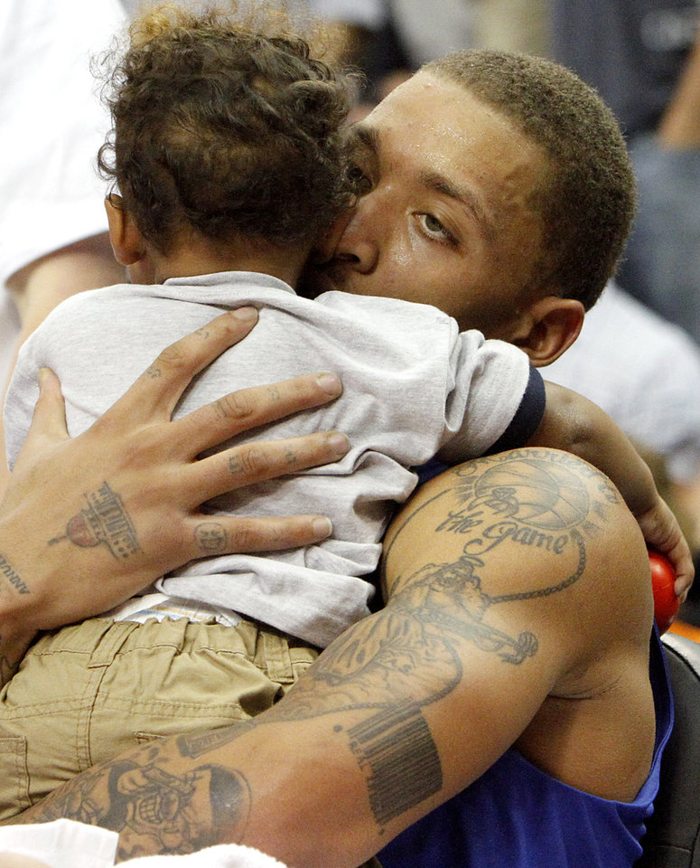 Photo - Sitting on the bench, Michael Beasley kisses his son Michael Beesley III, during the US Fleet Tracking Basketball Invitational at the Cox Convention Center in Oklahoma City Sunday, Oct. 23, 2011. The White Team defeated the Blue Team 176-171. Photo by John Clanton, The Oklahoman