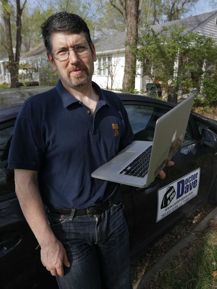 Photo -  Dave Greenbaum, who runs a computer repair business, poses for a photograph outside his house in Lawrence, Kan.  AP Photo   Orlin Wagner -  AP