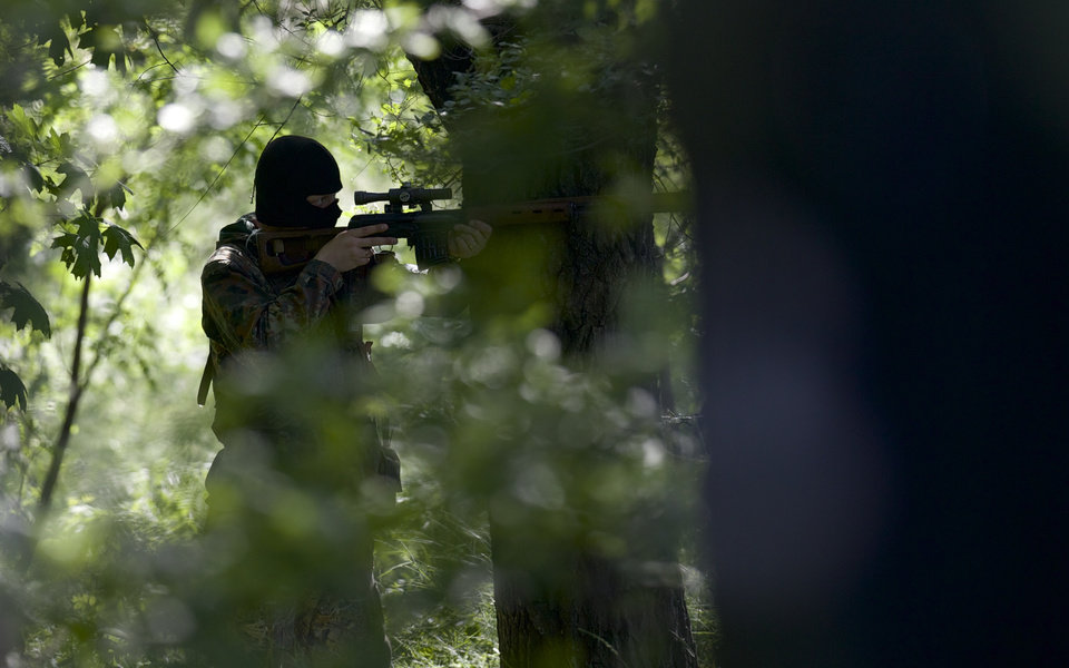 Photo - A pro-Russian insurgent aims his rifle during fighting around the airport outside Donetsk, Ukraine, Monday, May 26, 2014. Ukraine's military launched air strikes Monday against separatists who had taken over the airport in the eastern capital of Donetsk in what appeared to be the most visible operation of the Ukrainian troops since they started a crackdown on insurgents last month. (AP Photo/Vadim Ghirda)