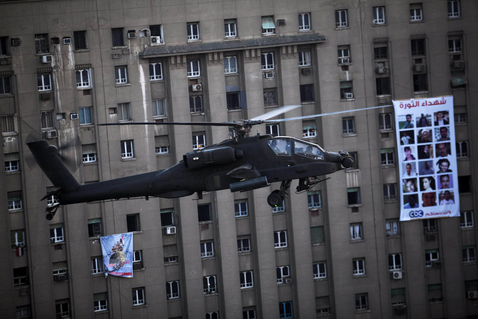 Photo - An Egyptian Army helicopter flies over thousands of supporters of Egypt's top military officer, Gen. Abdel-Fatah el-Sissi during a rally in Tahrir Square in Cairo, Egypt, Friday, July 26, 2013. Prosecutors opened an investigation of ousted President Mohammed Morsi on charges including murder and conspiracy with the Palestinian militant group Hamas, fueling tensions amid a showdown in the streets between tens of thousands of backers of the military and supporters calling for the Islamist leader's reinstatement. (AP Photo/Manu Brabo)