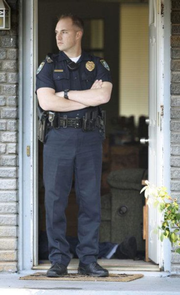 Photo - A Midwest City police officer stands watch in the doorway at the scene of a Thursday home invasion and shooting in Midwest City. The resident shot two people who broke into her house, killing a man and wounding a juvenile male. By Paul Hellstern, The Oklahoman ORG XMIT: KOD  PAUL HELLSTERN