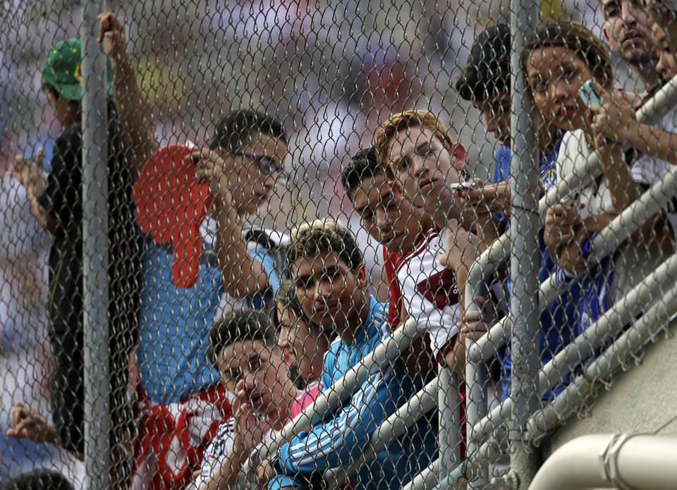 Photo - Fans line the gates along the tunnel entrance to the field at the Cotton Bowl stadium as they wait for Real Madrid and Roma players to make their way onto the field for a Guinness International Champions Cup soccer tournament match, Tuesday, July 29, 2014, in Dallas. (AP Photo/Tony Gutierrez)