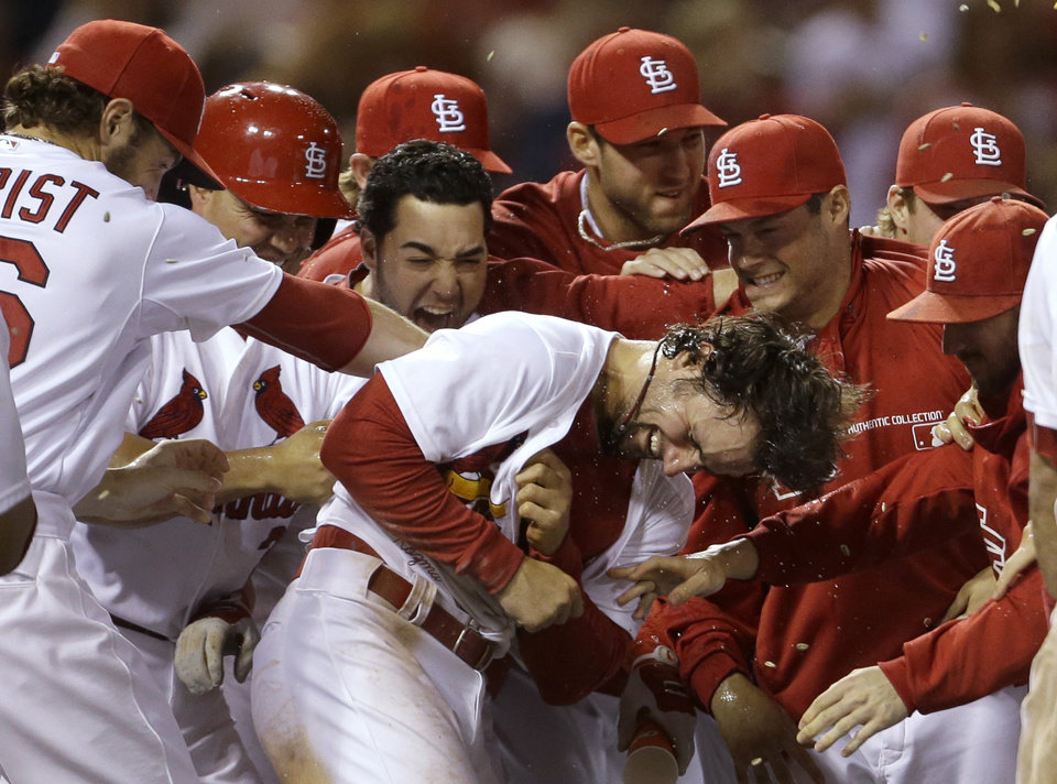 Photo - St. Louis Cardinals' Pete Kozma, center, is mobbed by teammates after scoring the game-winning run on a passed ball during the 10th inning of a baseball game against the Seattle Mariners on Friday, Sept. 13, 2013, in St. Louis. The Cardinals won 2-1. (AP Photo/Jeff Roberson)