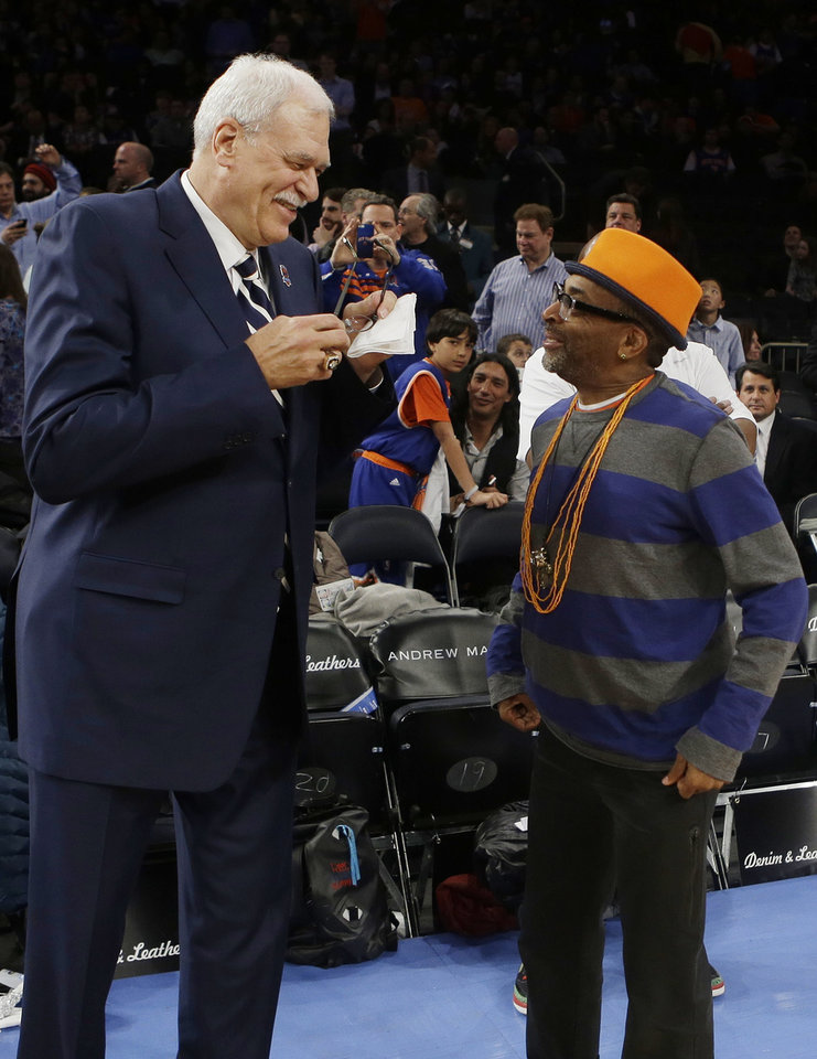 Photo - Former NBA coach Phil Jackson, left, and director Spike Lee, right, talk before a ceremony to honor the 1972-73 Championship New York Knicks team during the first half of an NBA basketball game between the Knicks and the Milwaukee Bucks, Friday, April 5, 2013, in New York. (AP Photo/Frank Franklin II)