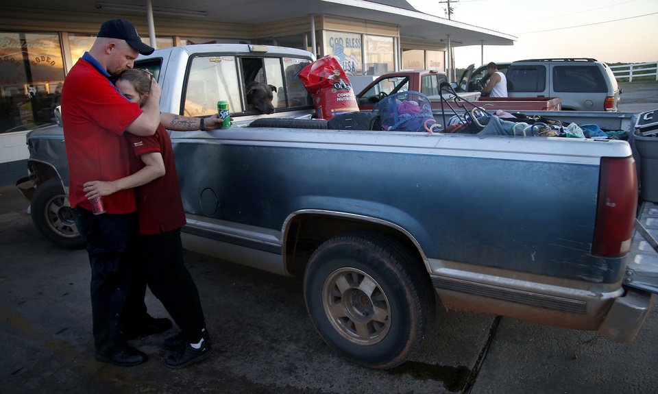 Photo - Right:  Alyssa Hutton and Jesse Cannon embrace Sunday in front of their truck, which was filled with the items they could grab after being evacuated from the wildfire zone in Logan County.  Photo by Sarah Phipps, The Oklahoman  SARAH PHIPPS