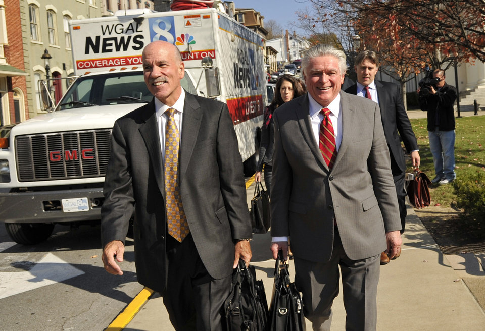 Photo - Attorneys for the NCAA Everett Johnson, left, and Tom Scott, right, exit the Centre County Courthouse, Tuesday, Oct. 29, 2013, in Bellefonte, Pa., after a court hearing. Lawyers for the NCAA, the Paterno family and Paterno supporters were at the Centre County Courthouse, Tuesday for a court hearing on whether to allow a lawsuit filed against the NCAA by the family of longtime Penn State football coach Joe Paterno and others to go forward. The lawsuit brought by the Paterno family aims to wipe out the NCAA sanctions against Penn State University.  (AP Photo/Centre Daily Times, Nabil K. Mark) MAGS OUT MANDATORY CREDIT