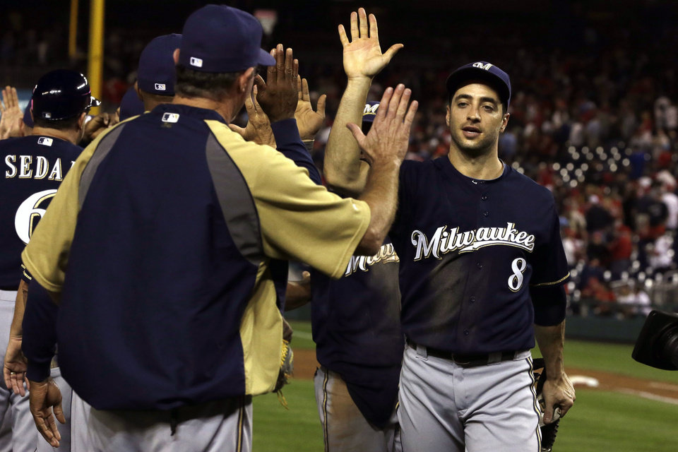 Photo -   Milwaukee Brewers Ryan Braun (8) high-fives teammates after they won their baseball game 4-2 against the Washington Nationals at Nationals Park in Washington, Friday, Sept. 21, 2012. (AP Photo/Jacquelyn Martin)