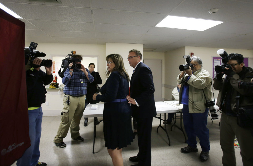 Photo - Lorraine Rossi Lonegan leads her husband Republican Senate candidate Steve Lonegan, who is legally blind, to a voting booth in Bogota, N.J., Wednesday, Oct. 16, 2013. Lonegan and Democrat Cory Booker are vying to fill the Senate seat left vacant by the death of Frank Lautenberg. (AP Photo/Mel Evans)