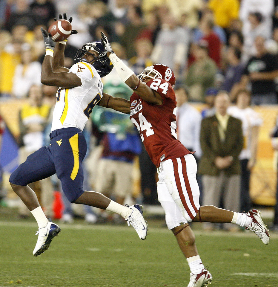 Photo - Quinton Andrews of West Virginia catches a touchdown pass in front of Marcus Walker during the second half of the Fiesta Bowl college football game between the University of Oklahoma Sooners (OU) and the West Virginia University Mountaineers (WVU) at The University of Phoenix Stadium on Wednesday, Jan. 2, 2008, in Glendale, Ariz. 