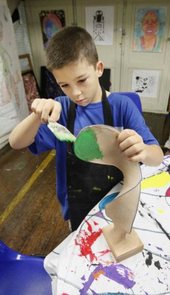 Photo - Taft Middle School seventh-grader  Eric Mullen, 12, paints a sculpture made from a coat hanger and pantyhose during the