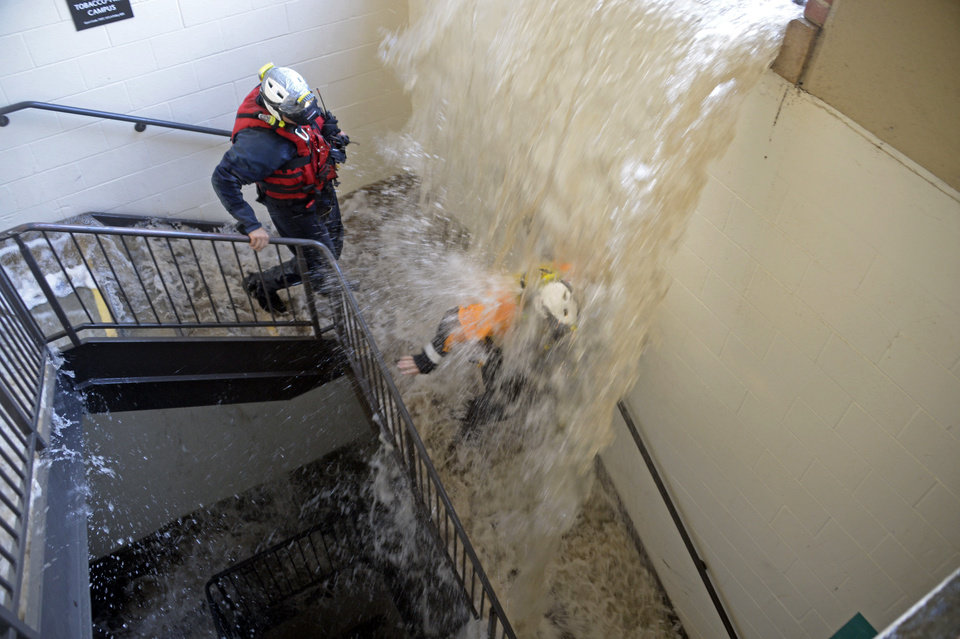 Photo - Workers walk down stairs to a parking structure as water cascades down on them on the UCLA campus after flooding from a broken 30-inch water main under nearby Sunset Boulevard inundated a large area of the campus in the Westwood section of Los Angeles, Tuesday, July 29, 2014. The 30-inch (75-centimeter)  93-year-old pipe that broke made a raging river of the street and sent millions of gallons (liters) of water across the school's athletic facilities, including the famed floor of Pauley Pavilion, the neighboring Wooden Center and the Los Angeles Tennis Center, and a pair of parking structures that took the brunt of the damage. (AP Photo/Mike Meadows)