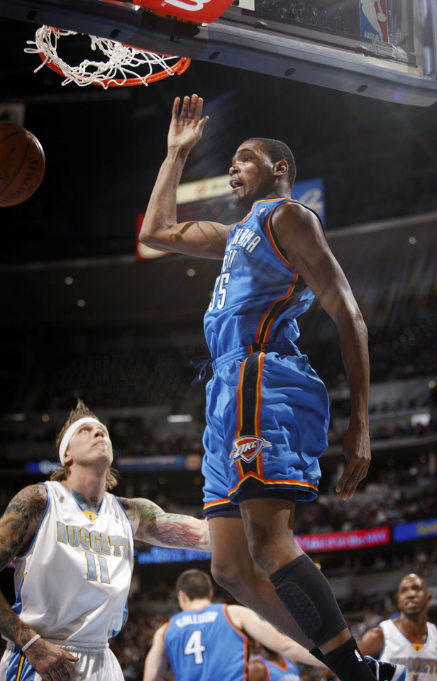 Photo - DUNK: Oklahoma City Thunder forward Kevin Durant, front, hangs in the air after dunking the ball for a basket over Denver Nuggets forward Chris Andersen in the first quarter of an NBA basketball game in Denver on Monday, Dec. 14, 2009. (AP Photo/David Zalubowski) ORG XMIT: CODZ101