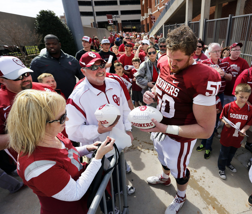 Photo - Austin Woods (50) signs autographs as fans line up behind him wating to enter the field for player autographs after the annual Spring Football Game at Gaylord Family-Oklahoma Memorial Stadium in Norman, Okla., on Saturday, April 13, 2013. Photo by Steve Sisney, The Oklahoman