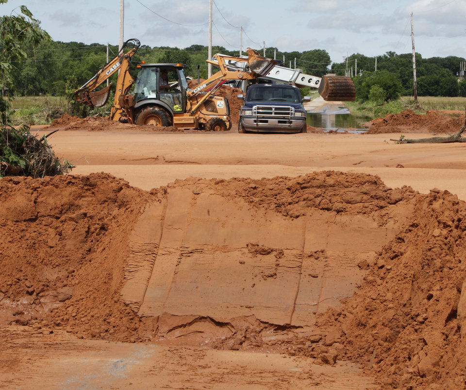 Photo - Edmond city workers scoop hundreds of tons of sand off of Danforth Rd. just west of Douglas in Edmond, OK, after yesterday's torential rains deposited the sand more than three feet deep across the road, Tuesday, June 15, 2010. By Paul Hellstern, The Oklahoman