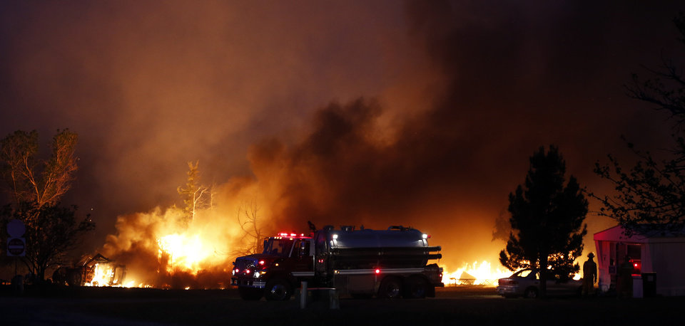 Photo - A fire burns in a mobile home park near Prairie Grove Rd. and Douglas during wildfires in Logan County, Sunday, May 4, 2014. Photo by Nate Billings, The Oklahoman