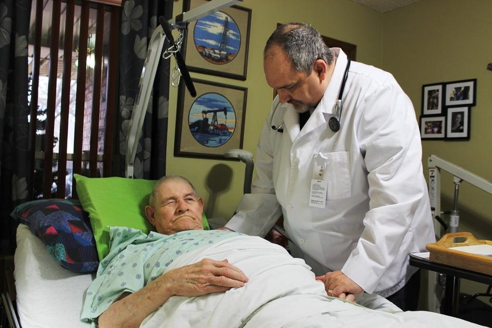 Photo -  Dr. Joe Witten, a primary care physician with Physician Housecalls, checks on Bob Littlejohn, a 77-year-old Oklahoma City resident who is largely homebound. Before signing up for the house calls service, Littlejohn's family had to call the fire department to move him from his bed. Photo Provided    Provided  -  Provided