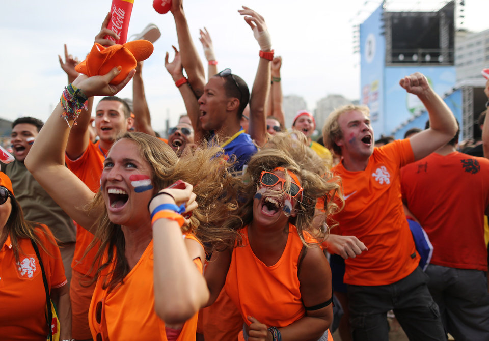 Photo - Soccer fans, decked out in orange, the Netherlands' national color, celebrate the second goal scored by Memphis Depay, while watching a live broadcast of the group B World Cup match between Chile and Netherlands, inside the FIFA Fan Fest area on Copacabana beach, in Rio de Janeiro, Brazil, Monday, June 23, 2014. Netherlands won 2-0, taking the top spot in group B. (AP Photo/Leo Correa)