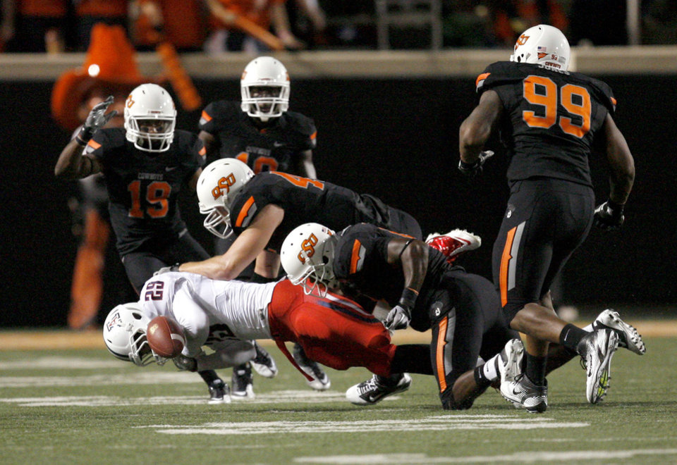Photo - The OSU defense forces Arizona's Austin Hill to fumble during the first half of their game Thursday in Stillwater. PHOTO BY SARAH PHIPPS, The Oklahoman