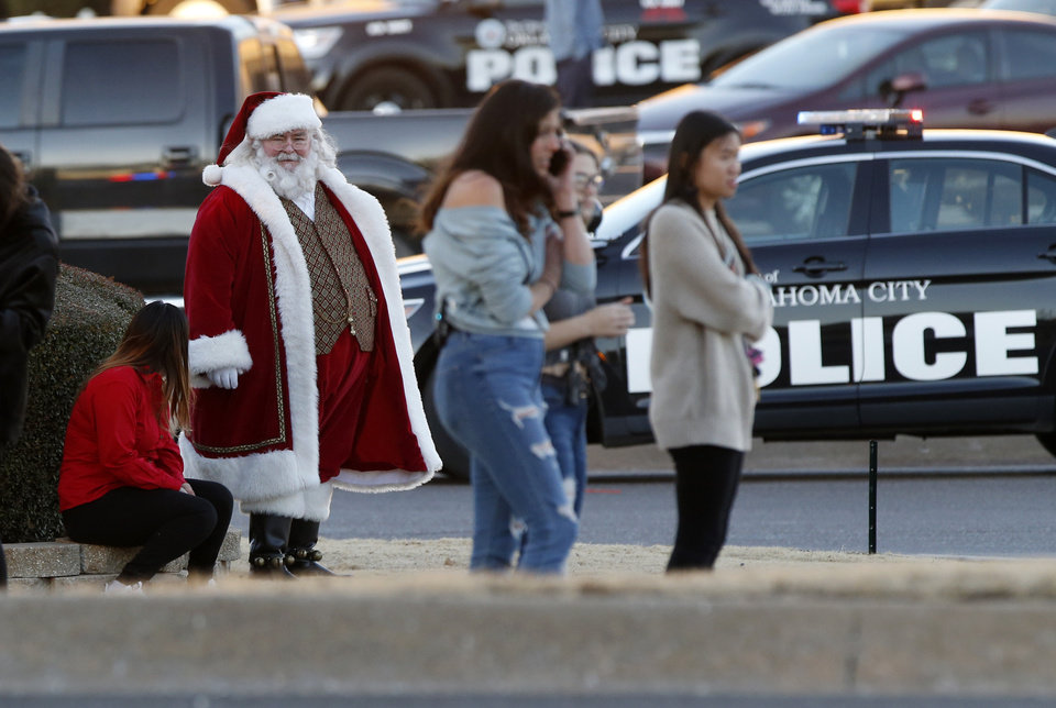 Photo - Santa Claus waits on the south side of Penn Square Mall with others who were evacuated after a shooting inside the mall in Oklahoma City, Thursday, Dec. 19, 2019. [Nate Billings/The Oklahoman]