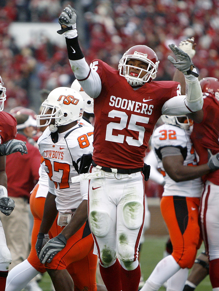 Photo - OU's D.J. Wolfe celebrats in front of Brandon Pettigrew of OSU after Wolfe recovered a fumble during the first half of the college football game between the University of Oklahoma Sooners (OU) and the Oklahoma State University Cowboys (OSU) at the Gaylord Family-Memorial Stadium on Saturday, Nov. 24, 2007, in Norman, Okla.  Photo By Bryan Terry, The Oklahoman