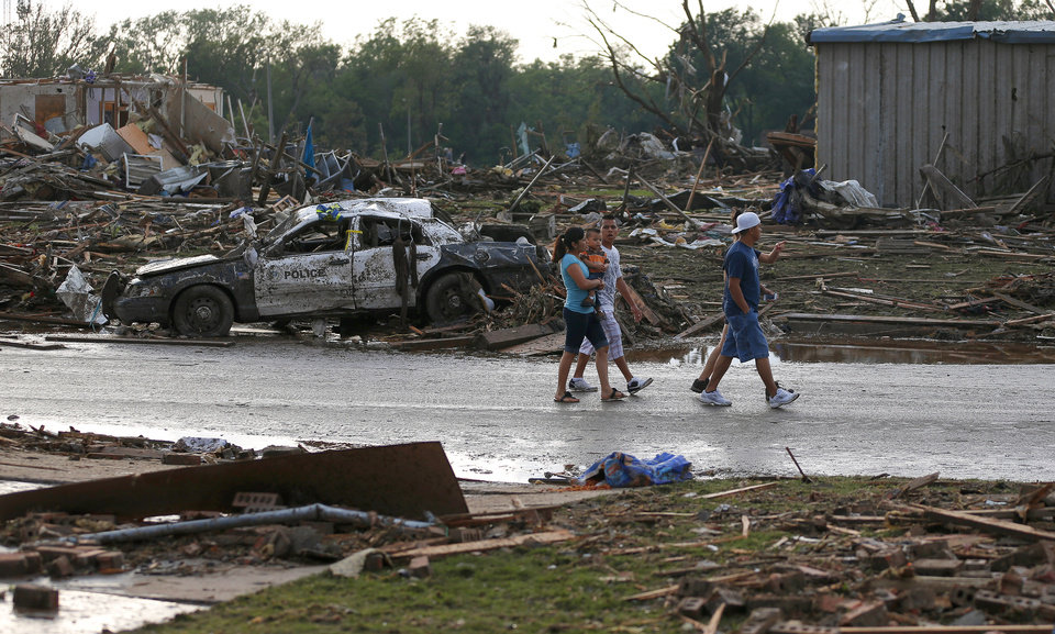 People walk down a street in a residential area just west of Telephone Road in Moore, Okla., after a tornado moved through the area on Monday, May 20, 2013. Photo by Bryan Terry, The Oklahoman