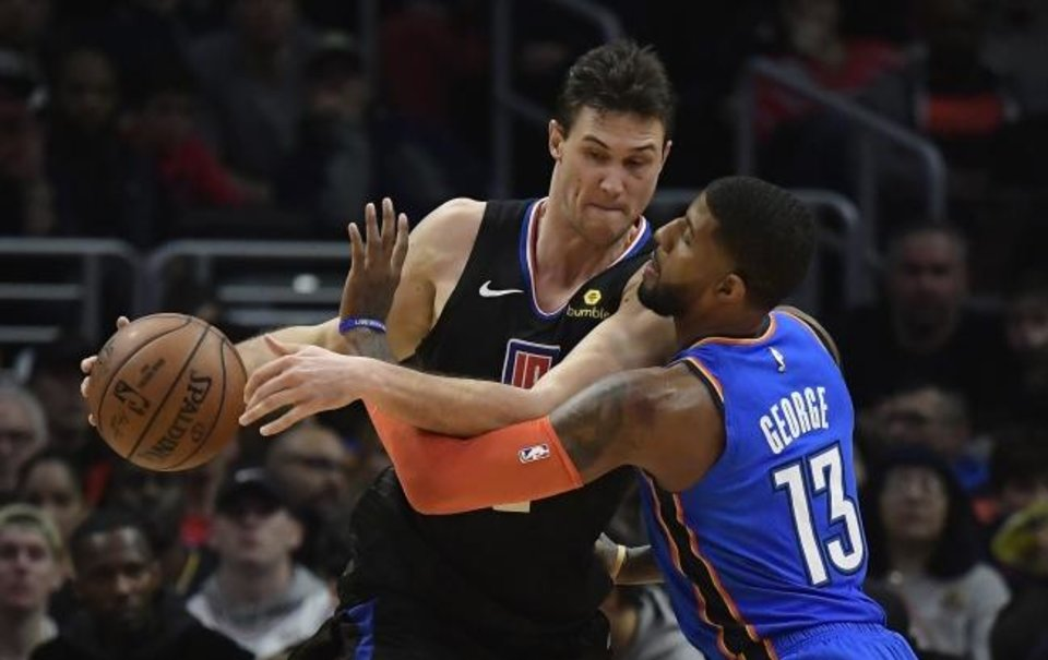 Photo -  Former Oklahoma City Thunder forward Paul George, right, reaches in on then-Los Angeles Clippers forward Danilo Gallinari during a game last March in Los Angeles. Gallinari is now a member of the Thunder.  [AP Photo/Mark J. Terrill]