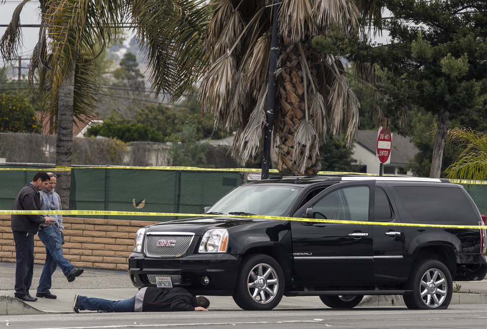 Photo - A police investigator looks under a disabled SUV left on Red Hill Ave. in Tustin, Calif., Tuesday, Feb. 19, 2013. Police say a chaotic 25-minute shooting spree through Orange County left a trail of dead and injured victims before the shooter killed himself.  There were multiple crime scenes in Tustin and Orange and many more victims who were shot at but unhurt, said Tustin Lt. Paul Garaven.  Tustin is about 35 miles southeast of downtown Los Angeles. (AP Photo/Damian Dovarganes)