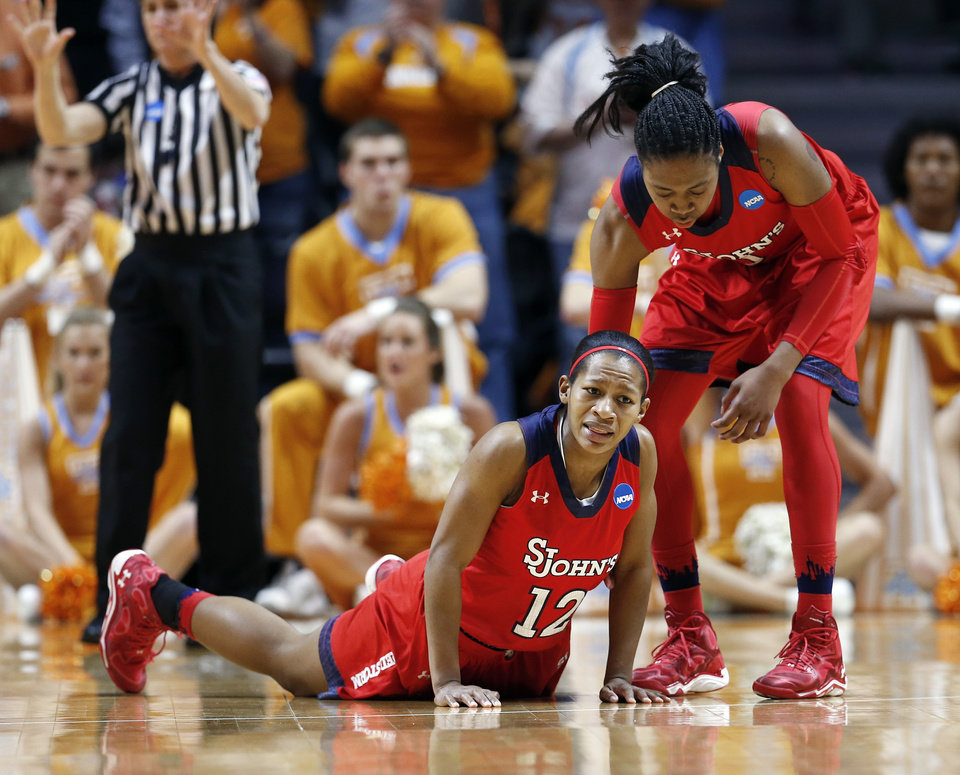 Photo - St. John's guard Briana Brown (12) is helped up by Amber Thompson in the second half of an NCAA women's college basketball second-round tournament game against Tennessee Monday, March 24, 2014, in Knoxville, Tenn. Tennessee won 67-51. (AP Photo/John Bazemore)
