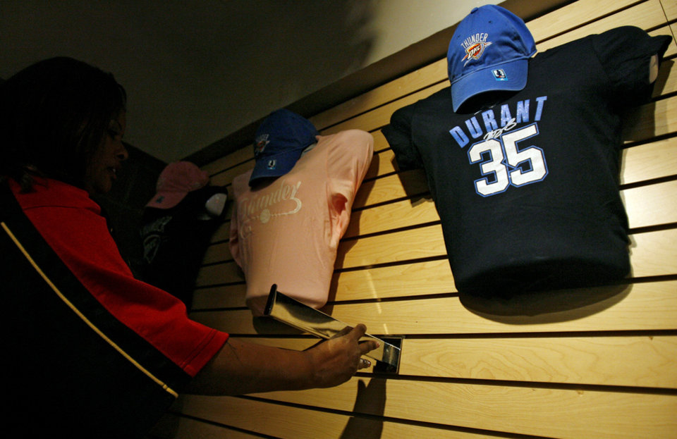 A merchandiser stocks the shelves with Thunder gear before the opening night NBA basketball game between the Oklahoma City Thunder and the Milwaukee Bucks on Wednesday, Oct. 29, 2008, at the Ford Center in Oklahoma City, Okla. BY CHRIS LANDSBERGER, THE OKLAHOMAN