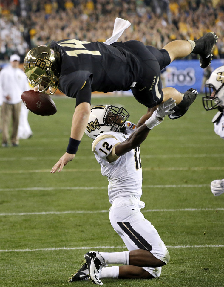 Photo - FILE - In this Jan. 1, 2014, file photo, Baylor quarterback Bryce Petty leaps over Central Florida defensive back Jacoby Glenn (12) for a touchdown during the first half of the Fiesta Bowl NCAA college football game in Glendale, Ariz. The senior was the Big 12 offensive player of the year after passing for 4,200 yards and 32 TDs _ with just three interceptions _ and running for 14 more scores. (AP Photo/Ross D. Franklin, File)