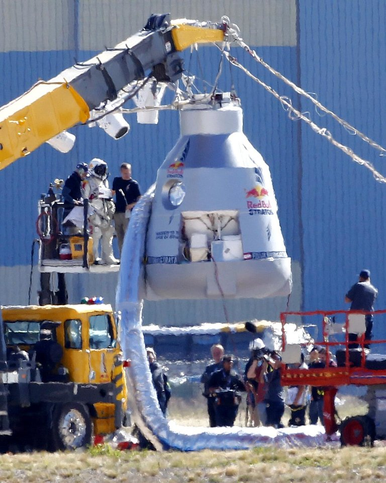 Photo -   Felix Baumgartner, in pressurized suit on platform at left, prepares to enter the balloon capsule in Roswell, N.M. on Tuesday, Oct. 9, 2012. Baumgartner will attempt to break the speed of sound with his own body by jumping from the space capsule lifted by a 30 million cubic foot helium balloon. Baumgartner plans to jump from an altitude of 120,000 feet - an altitude chosen to enable him to achieve Mach 1 in freefall - which will deliver scientific data to the aerospace community about human survival from high altitudes. (AP Photo/Matt York)