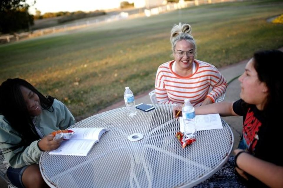 Photo -  Mentor Ruth Martin talks with Blessed Fields, left, and Sereniti Starr during an outdoors class [Sarah Phipps/The Oklahoman]