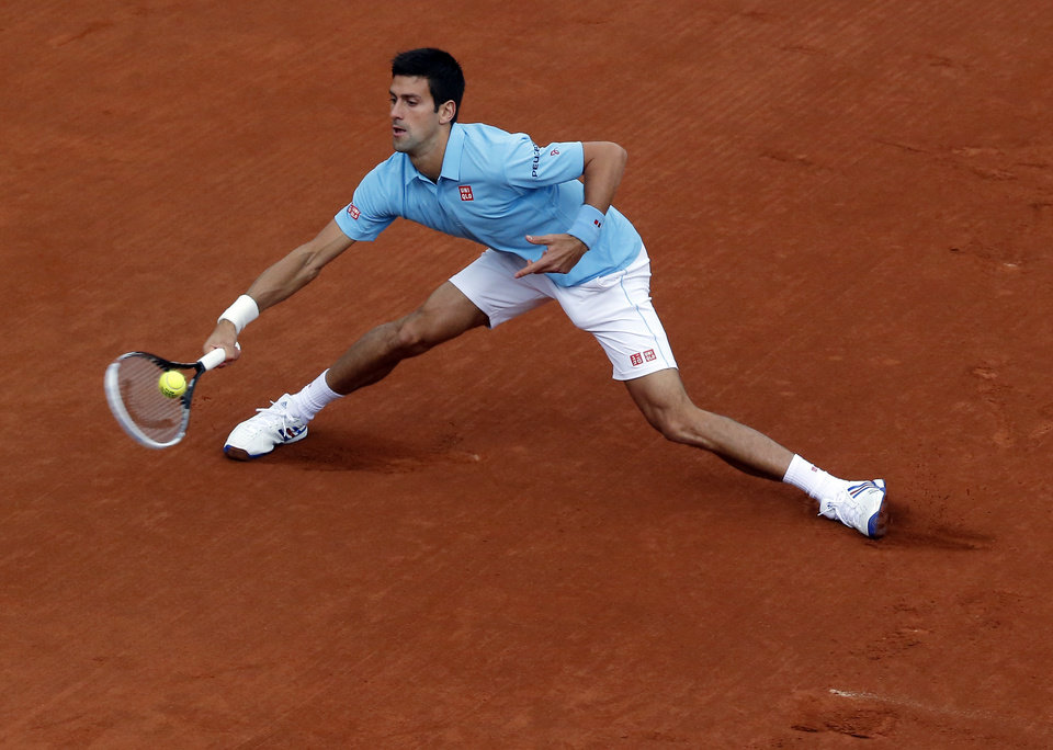 Photo - Serbia's Novak Djokovic returns the ball to Portugal's Joao Sousa during their first round match of  the French Open tennis tournament at the Roland Garros stadium, in Paris, France, Monday, May 26, 2014. (AP Photo/Michel Euler)